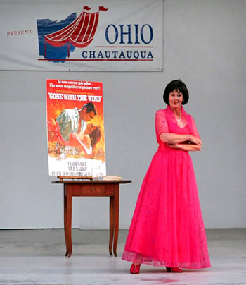 Adult woman wearing a pink dress standing on stage with poster gone with the wind